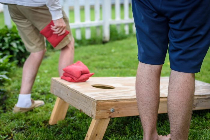 Two guys playing corn hole in the summer